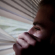 Man looking outside of window considering CBD Oil for anxiety