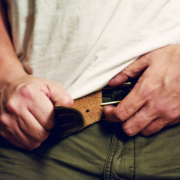 Man zipping up pants and considering cbd oil help with weight loss